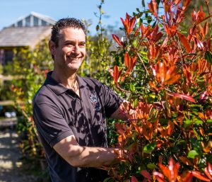 Rob Crowle wearing Duchy of Cornwall Nursery uniform and smiling while standing beside a red plant.