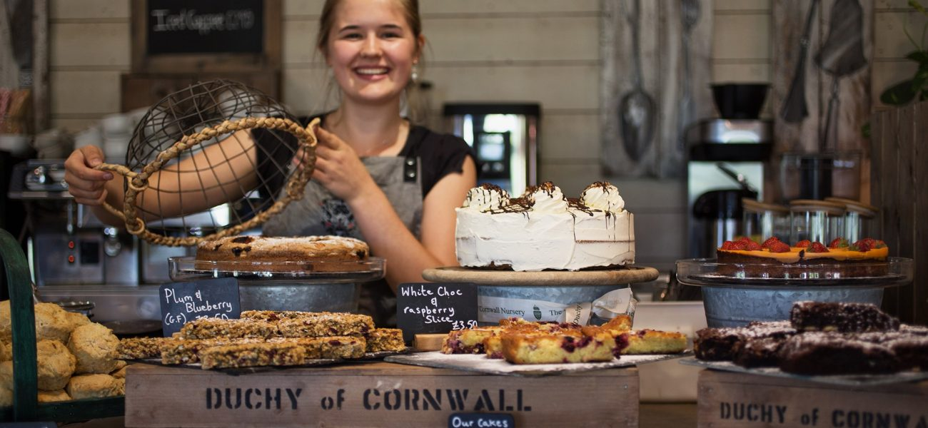 A member of staff at the Duchy of Cornwall nursery covering the cakes on display in the cafe.