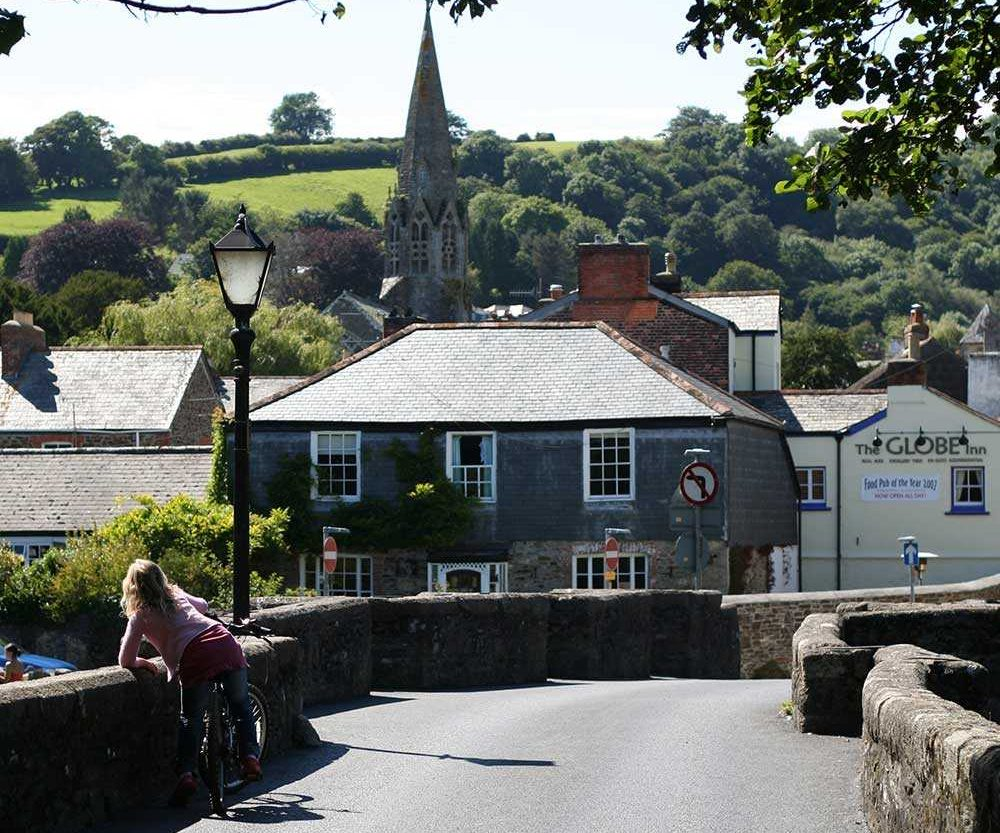 Bridge leading towards Lostwithiel, Cornwall with houses and a church behind.