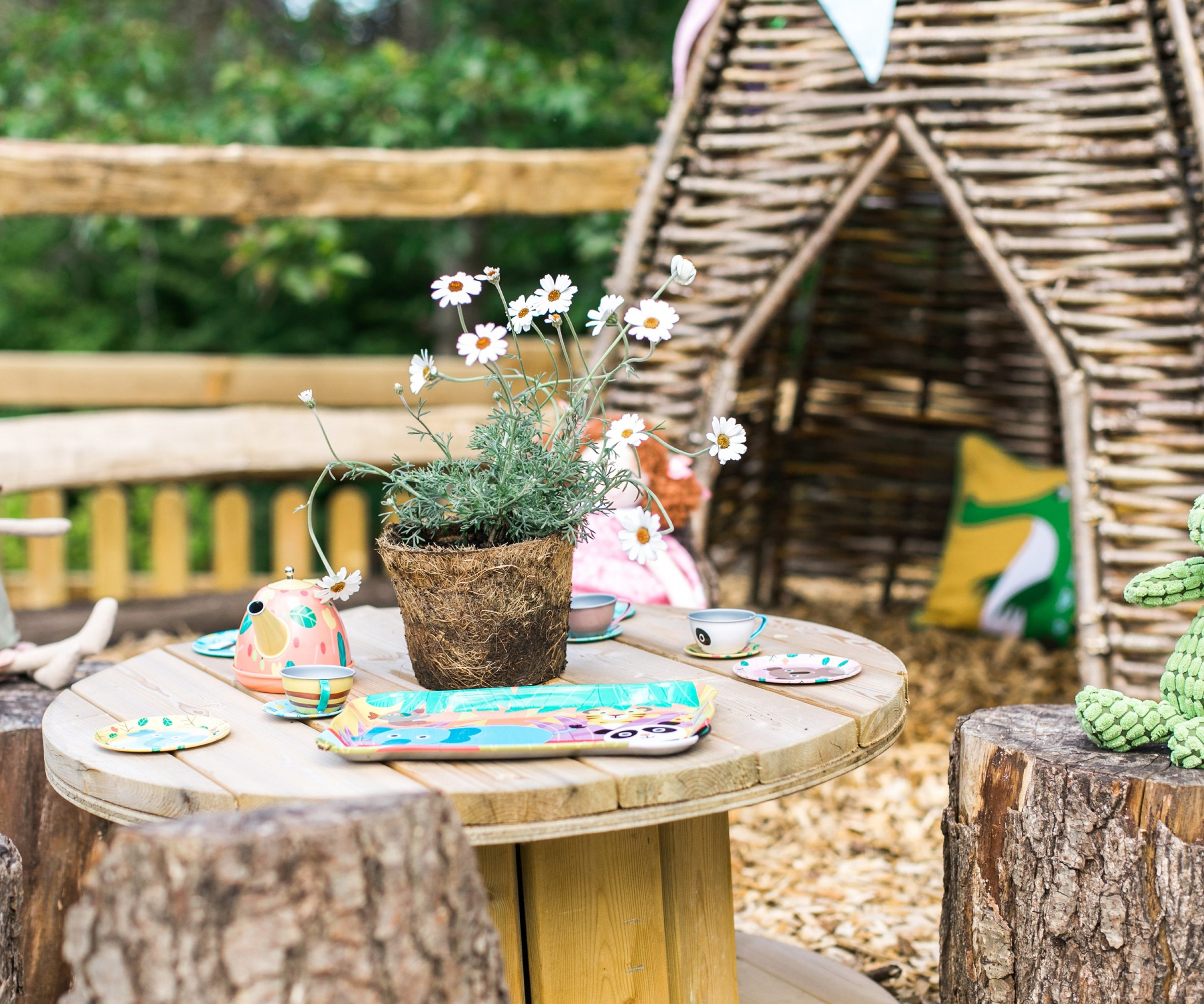 Handmade wooden miniature seating area and children's toys.