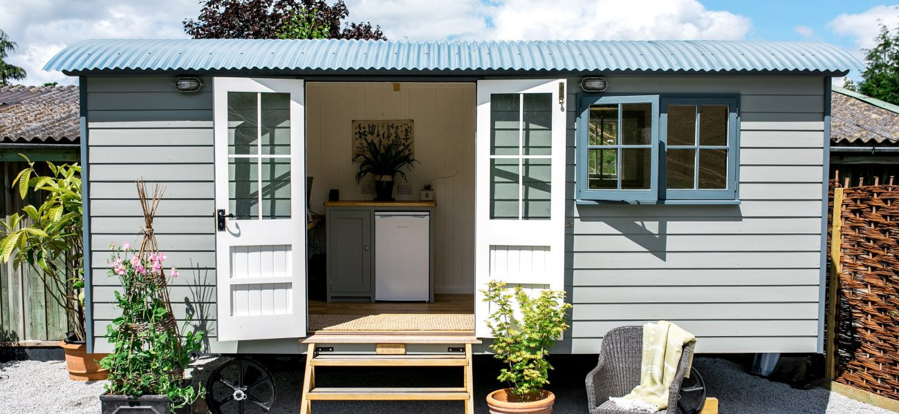 Grey exterior of a renovated shepherd's hut at the Duchy Nursery.