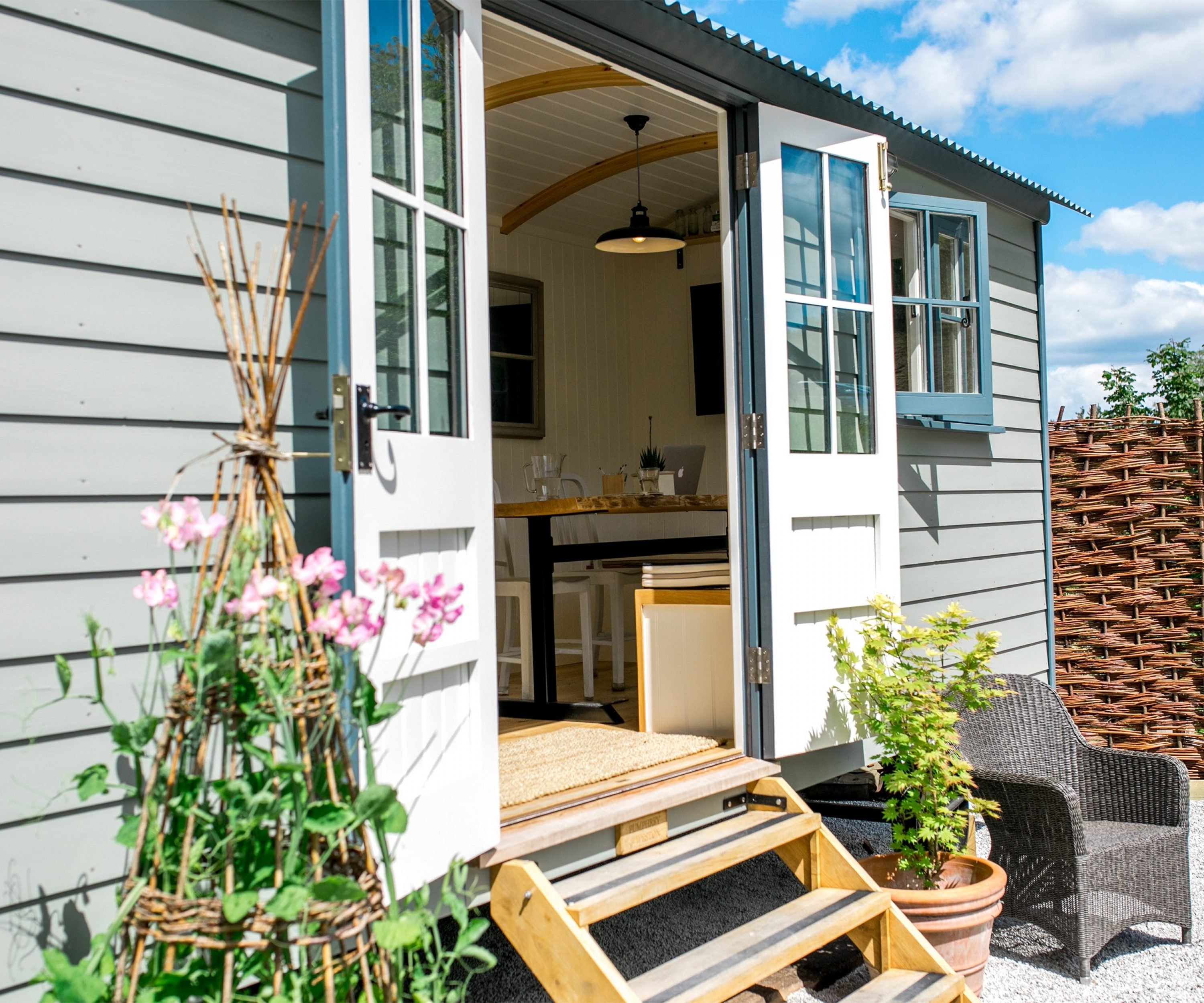 Open double doors on a renovated shepherd's hut with flowers growing outside.